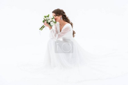 happy bride in traditional dress sniffing wedding bouquet, isolated on white
