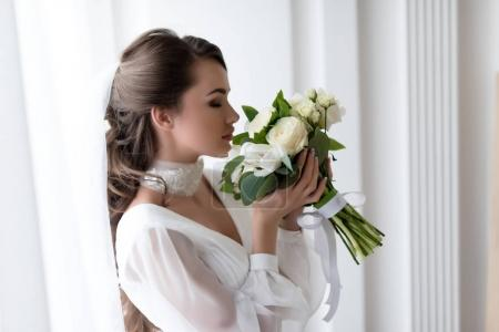 attractive bride in wedding dress and veil sniffing white bouquet
