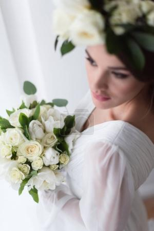 selective focus of young bride in floral wreath with wedding bouquet