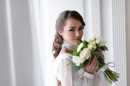 elegant smiling bride with wedding bouquet