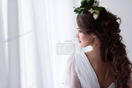 beautiful bride in traditional dress and floral wreath