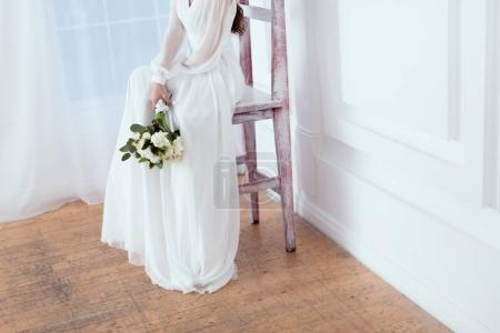 cropped view of elegant bride sitting on big chair with wedding bouquet