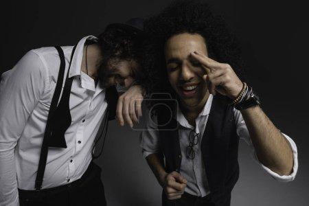 close-up shot of happy stylsih men looking at camera on black