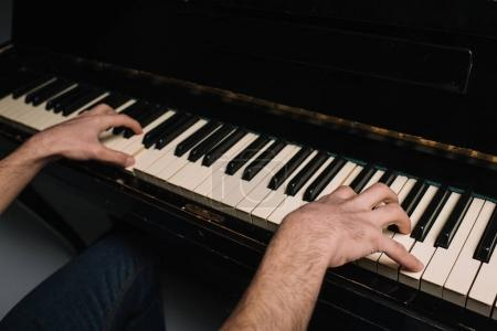 cropped shot of man playing piano
