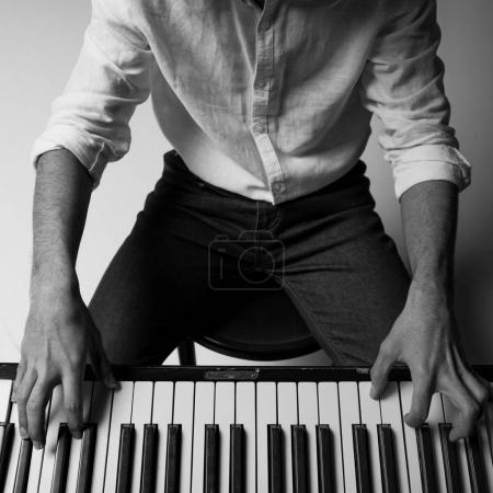 black and white cropped shot of man playing piano