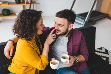 Woman touching nose of her boyfriend while holding coffee cups