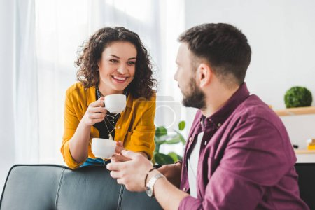 Woman holding coffee cups while talking with boyfriend