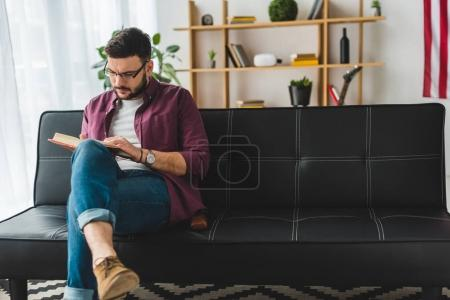 Front view of male in glasses reading book on couch