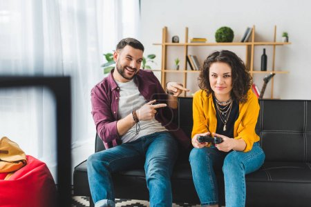 Man pointing fingers at his girlfriend while she holding joystick