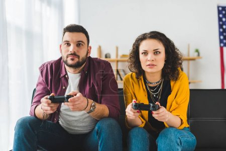 Front view of young couple holding joysticks in hands