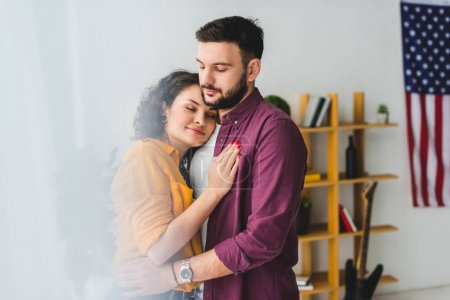 Young couple with closed eyes holding each other