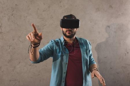 Photo pour Homme utilisant casque de réalité virtuelle et pointant du doigt - image libre de droit
