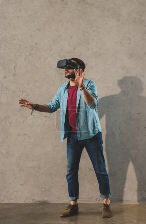 Young man standing in front of wall and using virtual reality headset