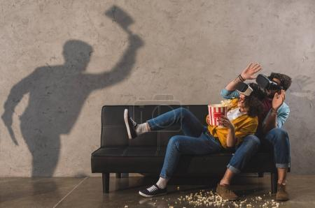 Shadow of man holding axe and scared couple with popcorns using virtual reality headset