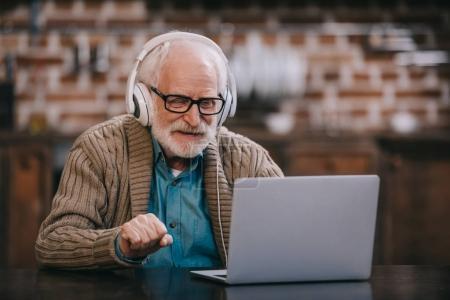 Senior man in headphones using laptop