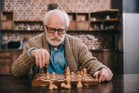 Clever senior man playing chess alone