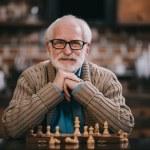 Senior man by chessboard looking at camera...