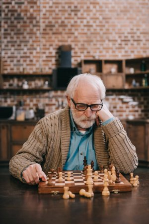 Thoughtful elder man by chess board