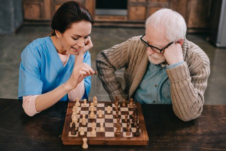Top view of nurse and elder man playing chess