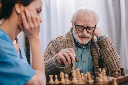 Senior man enjoying playing chess with nurse