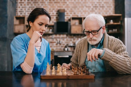 Photo for Old man and female caregiver playing chess - Royalty Free Image