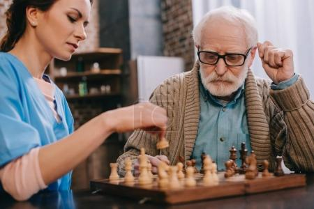 Nurse and senior man playing chess