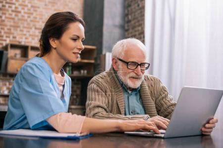 Photo pour Infirmière assise par un homme âgé utilisant un ordinateur portable - image libre de droit
