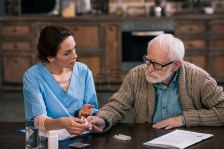 Photo for Female nurse giving pills to senior patient - Royalty Free Image