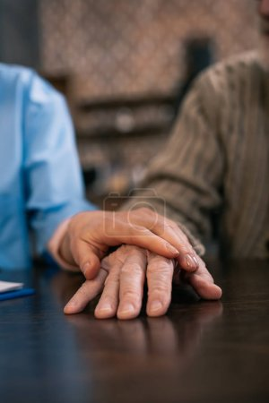 Caregiver supporting and holding hand of senior man