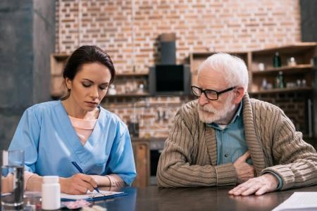 Photo pour Infirmière écrire seniors plaintes médicales des patients - image libre de droit