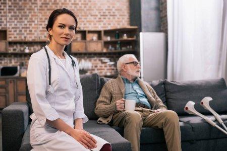 Female doctor in white coat sitting by senior man on sofa
