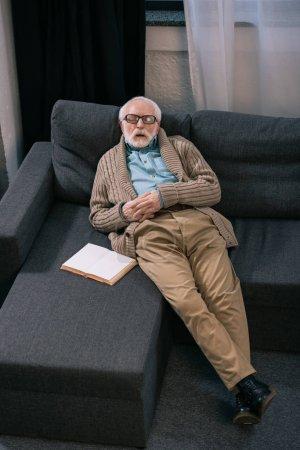 Senior man sleeping on sofa with book