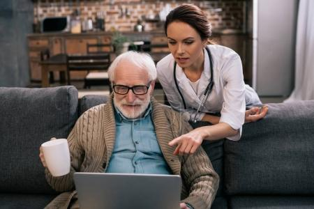 Doctor pointing at laptop in senior patient hands