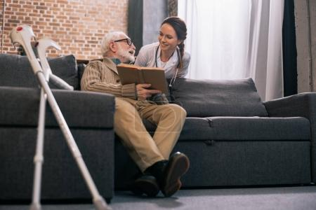 Senior male patient with book talking to smiling doctor