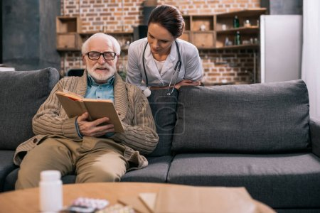 Senior man and female doctor reading book
