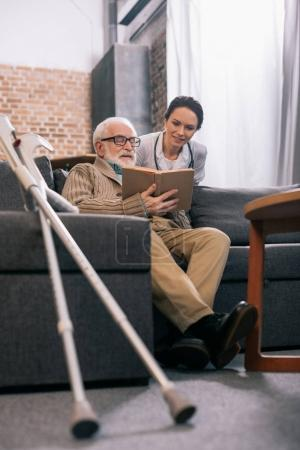 Female doctor standing by senior patient reading book