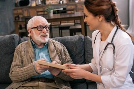 Doctor presenting book to senior man
