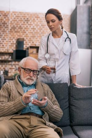 Doctor giving a glass of water to senior patient with pills