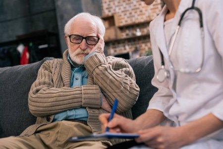 Photo pour Triste homme âgé regardant le médecin écrire des plaintes médicales - image libre de droit