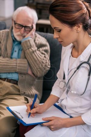 Photo pour Médecin féminin écrivant des plaintes médicales de patients âgés - image libre de droit
