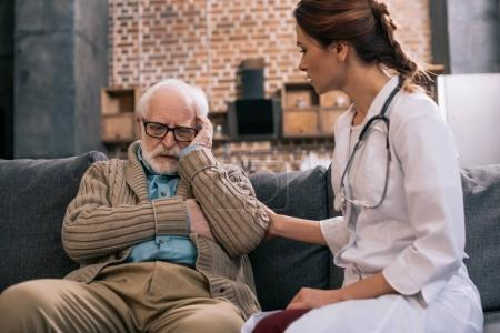 Female doctor supporting sad senior man
