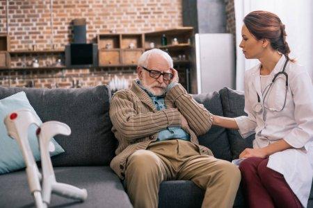 Female doctor reassuring upset old man