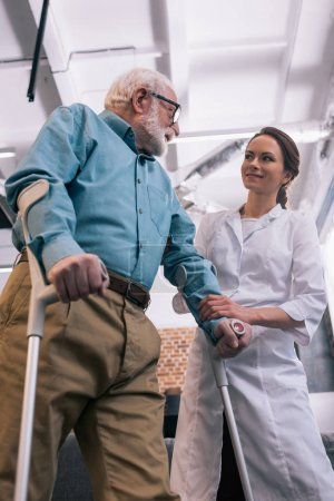 Senior man leaning on crutches and smiling female doctor