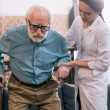 Old man leaning on cane and female doctor hand...