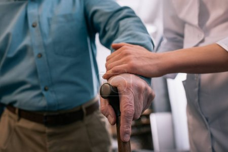 Photo for Close-up view of cane in hand of senior man supported by doctor - Royalty Free Image