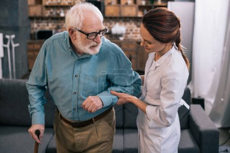 Doctor holding senior man hand with cane