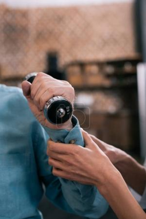 Close-up view of doctor helping senior man exercising with dumbbell