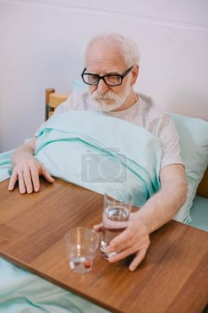 Old man in clinical bed taking medications