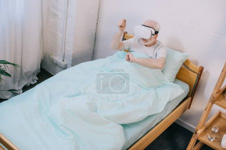 Senior man patient in clinical bed using vr headset