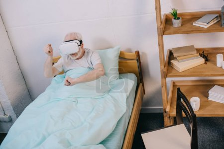 Old man using virtual reality headset in clinical bed